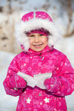 Happy laughing child in winter clothes with piece of ice Royalty Free Stock Photo