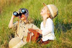 Happy laughing children. Cute children having fun and laughing together outdoors with binoculars and safari hats stock photography