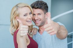 Happy laughing couple giving a thumbs up Stock Images