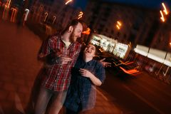 Happy laughing couple in motion. Youth nightlife. Romantic date outdoors, blurred lights urban background. Cheerful hugging people, fun concept Royalty Free Stock Photos