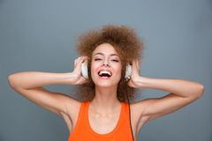 Happy laughing curly girl listening to music using headphones Royalty Free Stock Photography