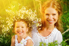 Happy laughing daughter hugging mother in wreaths of summer flow. Happy laughing family, daughter hugging mother in wreaths of summer flowers in nature Stock Photography