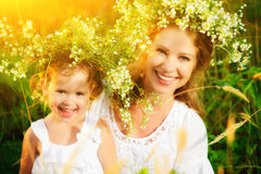 Happy laughing daughter hugging mother in wreaths of summer flow. Happy laughing family, daughter hugging mother in wreaths of summer flowers in nature Stock Photo