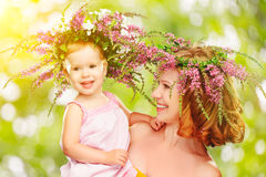 Happy laughing daughter hugging mother in wreaths of summer flow. Happy laughing family, daughter hugging mother in wreaths of summer flowers in nature Stock Photos