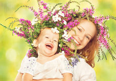 Happy laughing daughter hugging mother in wreaths of summer flowers. Happy laughing family, daughter hugging mother in wreaths of summer flowers in nature Stock Image