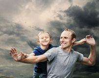 Happy laughing father with son with stormy sky background Stock Image