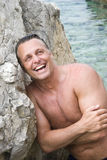 Happy laughing forties man. A color portrait photo of a handsome sexy mature man in his forties having fun at the beach Stock Images