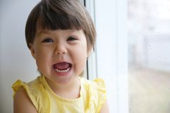 Happy laughing funny face little girl portrait. happy smiling child. Happy laughing funny face little girl portrait on window longing for some sunshine. happy Stock Photos