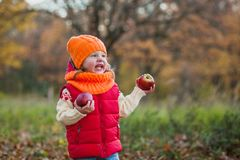 Happy laughing girl with apples on a walk in the autumn park royalty free stock photos