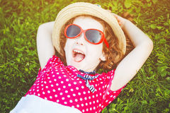 Happy laughing girl with glasses lying on the grass in a summer Stock Image