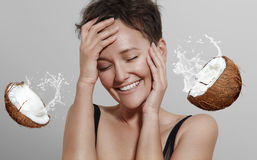 Happy laughing girl on a grey background with a coconut spread Stock Photo