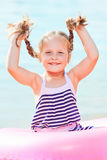 Happy laughing girl holds pigtails. toned image Stock Photos