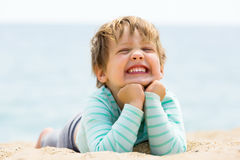 Happy laughing girl laying on sand beach Royalty Free Stock Image