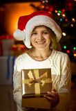 Happy laughing girl in Santa cap holding golden gift box Royalty Free Stock Photos