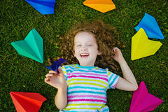 Happy laughing girl throwing paper airplane in green grass at su Stock Photo