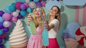 Two girls drinking juice from glass bottles. Candy. Happy laughing girls in colorful bright clothes drink a cocktail of glass bottles and clink on the camera stock video