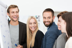 Happy laughing group of businesspeople. Happy laughing group of diverse young professional businesspeople standing together in front of a flip chart during a Stock Photo