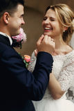 Happy laughing handsome groom and gorgeous emotional bride in wh Stock Photo