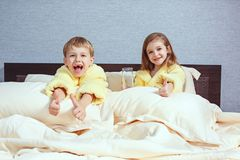 Happy laughing kids, boy and girl in soft bathrobe after bath play on white bed stock photography