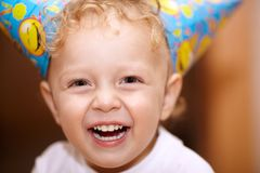 Happy laughing little boy. Closeup facial portrait of a happy laughing little boy with wavy blond hair looking directly into the camera Stock Images