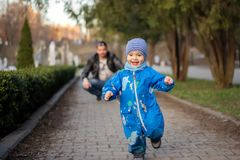 Happy laughing little boy playing with father in the park, running away from him. Active family leisure royalty free stock image