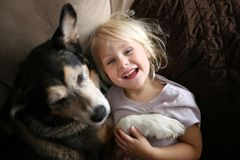 Happy, Laughing Little Girl Child Hugging Pet Dog on Couch. A happy, smiling little girl child is hugging her pet dog as they snuggle at home on the couch stock image