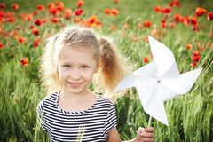 Happy laughing little girl  on the poppy meadow Stock Photo