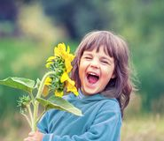 Free Happy Laughing Little Girl With A Sunflower Royalty Free Stock Photography - 127093017