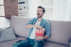 Happy laughing man in checkered shirt eating popcorn while watch. Ing comedies and having fun Royalty Free Stock Photos