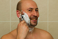 Happy laughing man shaving his face Royalty Free Stock Photos