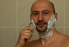 Happy laughing man shaving his face Stock Photo