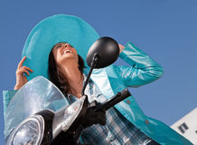 Happy laughing moped. Happy woman with blue raincoat and hat sitting on moped laughing Stock Photo