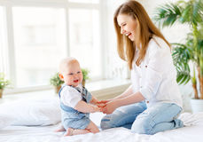 Happy laughing mother and baby playing in bed Royalty Free Stock Images