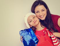 Happy laughing mother hugging with love her cute daughter in santa clause hat and holding Christmas present packages royalty free stock photography