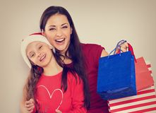 Happy laughing mother with open mouth hugging with love her cute joying daughter in santa clause hat and holding Christmas present stock photography