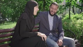 Happy laughing muslim couple sitting on bench in park and chatting. Portrait of joyful loving bearded man and woman in