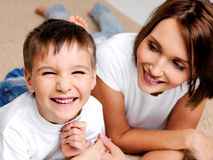 Happy laughing preschooler boy with his mother. Portrait of a happy laughing preschooler boy with his pretty young mother lying on the floor stock image