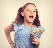 Happy laughing rich kid girl holding money the hand. Toned vinta stock images