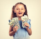 Happy laughing rich kid girl holding money in the hand. Vintage stock photos