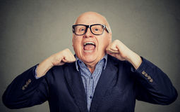 Happy laughing senior old man with hands up. Portrait of happy laughing senior old man with hands up isolated on gray background royalty free stock image