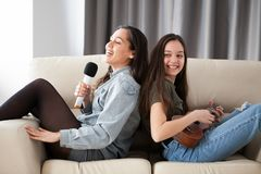 Happy laughing sisters on the couch in the living room. One is playing at the ukulele and the other is singing at the microphone royalty free stock images