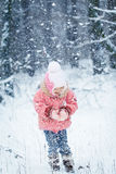 Happy laughing toddler girl in a beautiful snowy winter forest Royalty Free Stock Image