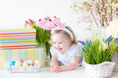 Happy laughing toddler girl with eggs spring flowers. Happy laughing toddler girl with curly hair wearing a blue dress and bunny ears playing with Easter Royalty Free Stock Image