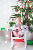 Happy laughing toddler girl playing with Christmas lights Stock Images