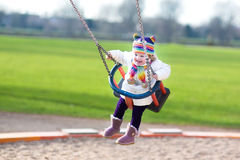 Happy laughing toddler girl swinging on playground. Happy laughing little toddler girl swinging on a playground Stock Images