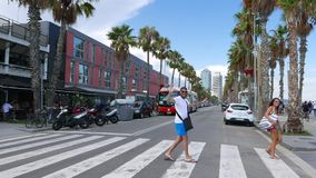 Happy laughing tourists cross road at Barceloneta Beach, Barcelona. Barcelona, SPAIN - AUGUST, 18, 2018: Happy laughing tourists cross road at Barceloneta Beach stock video footage
