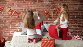 Happy laughing Triplets sisters in pajamas having a pillow fight in bed at home. The bedroom is decorated by christmas stock footage