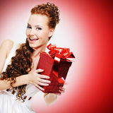 Happy laughing woman with birthday present in hands. Posing over red background royalty free stock photography