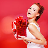 Happy laughing woman with birthday present in hands. Posing over red background royalty free stock photos