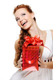 Happy laughing woman holding the red present. Happy laughing woman holding the present and looking up over white background Stock Image